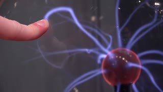 Finger pressing against plasma ball 4k