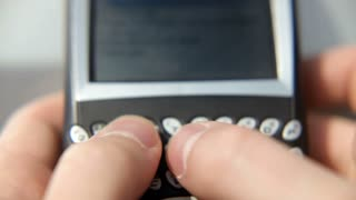 Fingers typing on cell phone keypad