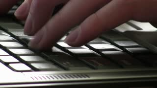 Fingers typing on keyboard