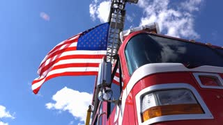 Firetruck parked outdoors with American flag waving on blue sky 4k