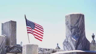 Flag blowing in wind with Father headstone at cemetery 4k