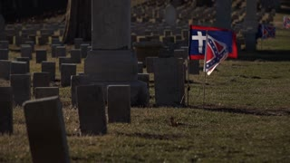 Flags waving at grave stones in cemetery 4k