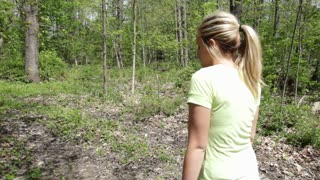 Following girl walking through woods.