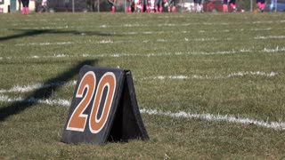 Football field 20 yard line marker with teams in background 4k
