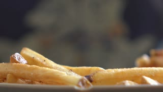 French Fries being eaten from plate with fork 4k