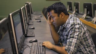 Frustrated Indian man at computer screen