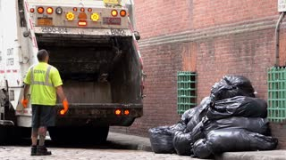Garbage truck backs up to stacks of trash bags in NYC 4k