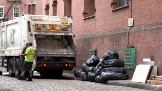 Garbage truck compacting trash bags in New York City 4k