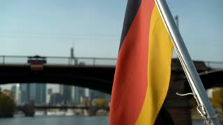 German flag on back of boat waving as it leaves the city 4k
