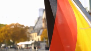 German flag waving in wind with town in background 4k
