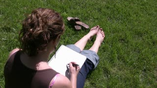 Girl drawing in Grass on Sunny Day.