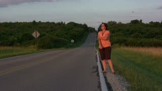 Girl hitch hiking on side of road