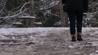 Girl in boots walking down ice covered ground