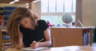 Girl in University Library taking notes with pencil 4k