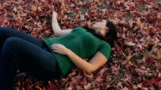Girl laying in fall leaves on ground