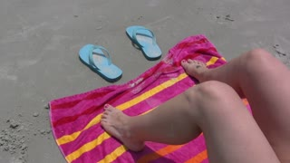 Girl laying on beach towel, wiggling toes.