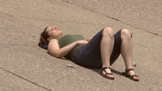 Girl laying on Concrete in Sun