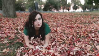 Girl laying on stomach in pile of leaves
