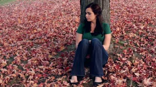 Girl leaning up against tree sitting Fall leaves