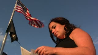 Girl looking at letters in front of flag