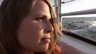 Girl looking into sunset off side of boat on ocean 4k