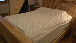Girl Making Bed in bedroom of home