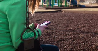 Girl on swing texting at playground 4k