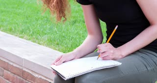 Girl outdoors writing in notebook with pencil 4k