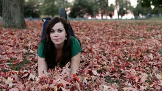 Girl piling up stacks of leaves and laying on them