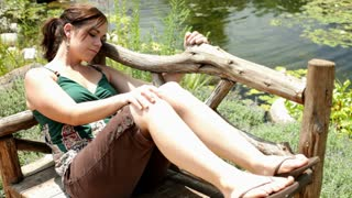 Girl relaxing on park bench with eyes closed