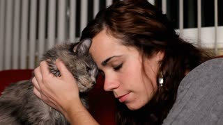 Girl rubbing heads with gray Cat