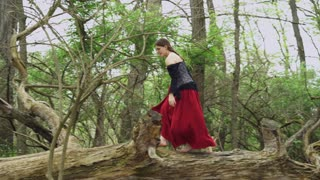 Girl running through wooded area in renaissance dress 4k