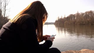 Girl sitting along river texting on cell phone 4k