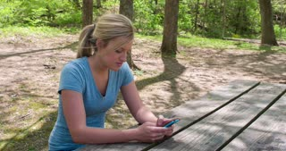 Girl sitting at bench in woods texting 4k.