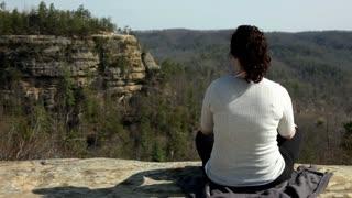 Girl sitting cross legged on rock