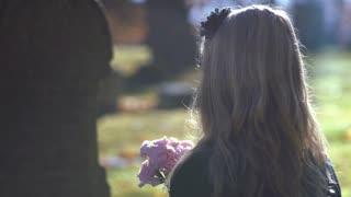 Girl sitting in sunshine in front of grave 4k