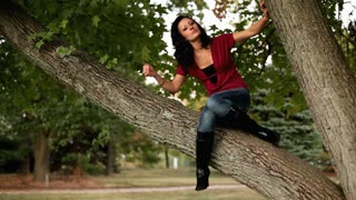 Girl sitting in tree playing with hair