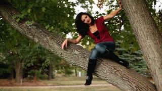 Girl sitting in tree swinging leg