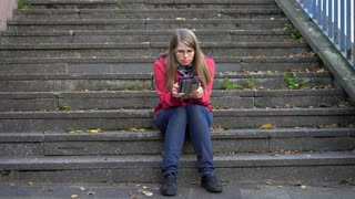 Girl sitting on stairs reading ebook on tablet 4k