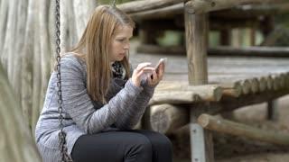 Girl sitting on swing in park using cell phone 4k