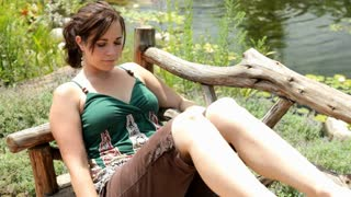 Girl sitting on wooden bench with eyes closed