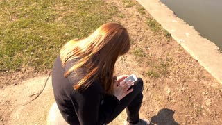 Girl sitting outdoors using cell phone to browse internet 4k