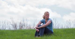 Girl smiling sitting in grass 4k