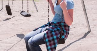 Girl smiling while on playground swing 4k