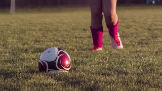 Girl soccer player kicking ball in grass slow motion