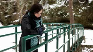 Girl standing against bridge rail in Snow Forest