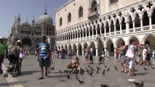 Girl surrounded by pigeons in Venice