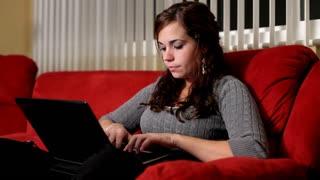 Girl using computer on red couch