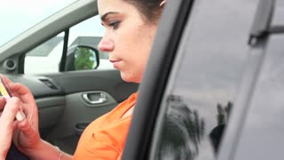Girl using smart phone sitting in car