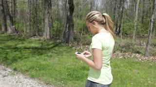 Girl walking and texting by woods